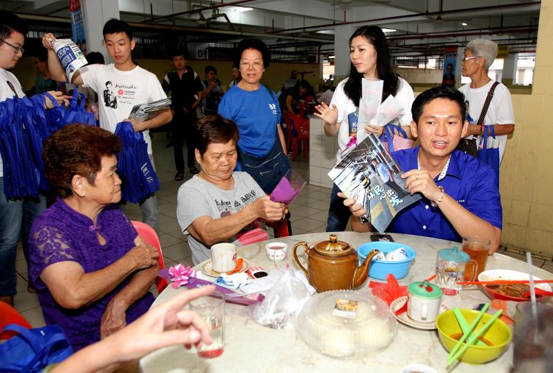 (right in blue seated) MCA candidate for the Selayang parliamentary seat Kang Meng Fuat meeting voters at the Rawang market.