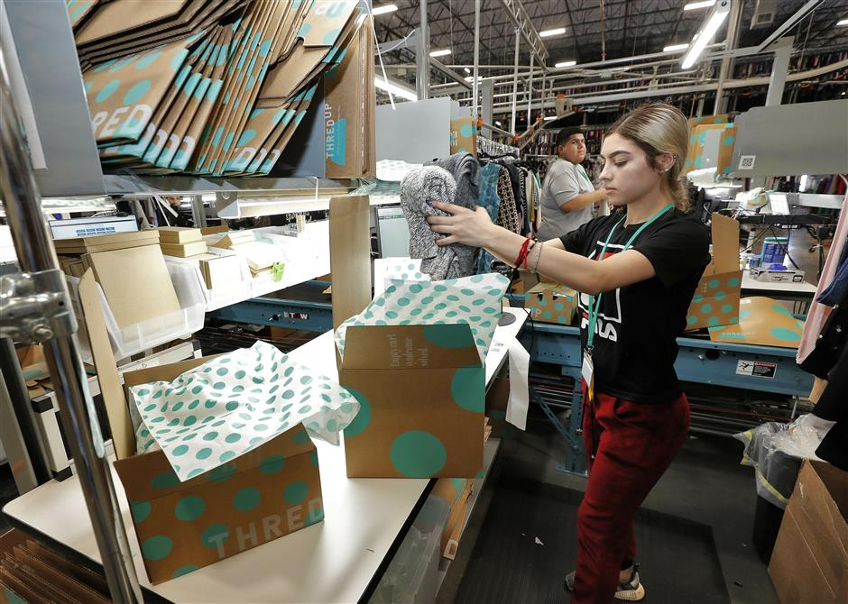In this Tuesday, March 12, 2019, photo Yakaranday Arce packs sold clothing for shipment at the ThredUp sorting facility in Phoenix. Charitable organizations like Goodwill have cited how Marie Kondou2019s popular Netflix series, u201cTidying up with Marie Kondou201d has led to a surge of donations. And sites like OfferUp and thredUP also note an uptick in the number of items being sent to them for sale. (AP Photo/Matt York)