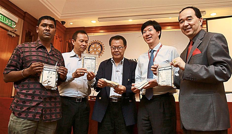 (From left) Kasih Sayang welfare home owner Ragu, Keh, Don Law, Ong and Chang with the rice-soy meal packets.Representatives of the organisers (from left) Keh, Don Law, Ong and Chang during the sponsorship presentation ceremony.