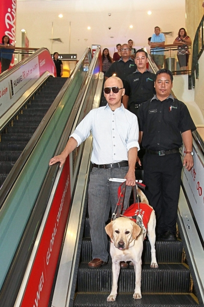 Chan and his guide dog Lashawn being escorted by security guards at a shopping centre in Seri Kembangan. — Filepic