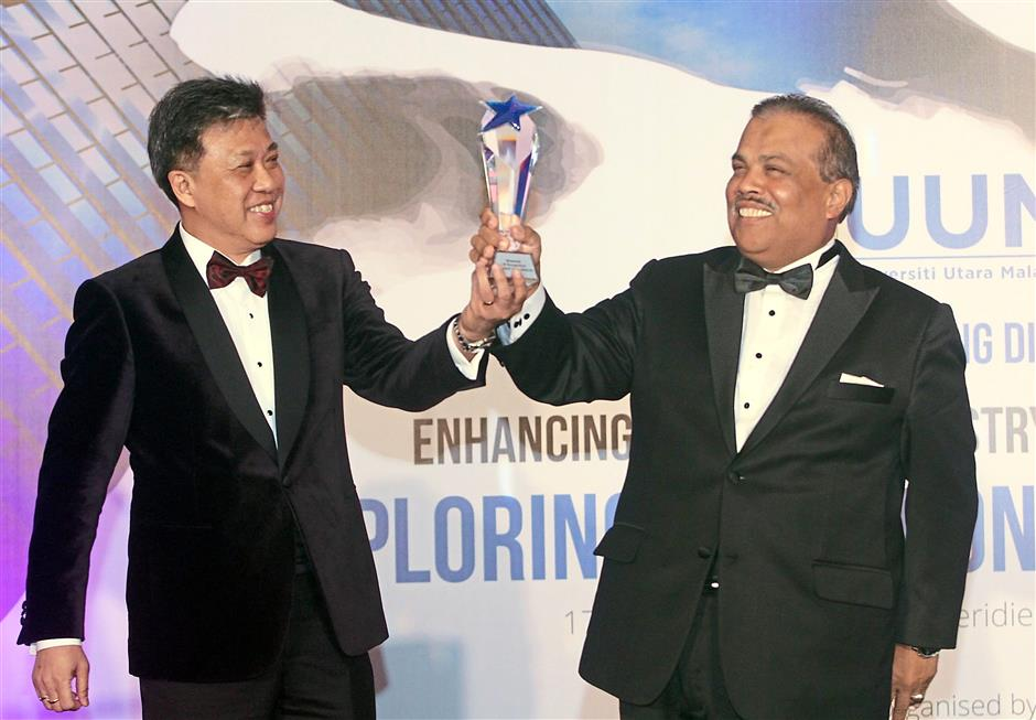 Wong (left) presenting a memento of recognition to Prof Mohamed Mustafa.