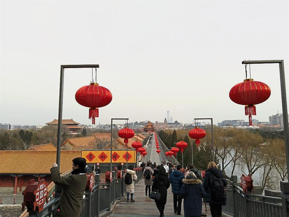 Visitors walking down a corridor decorating with red lanterns.