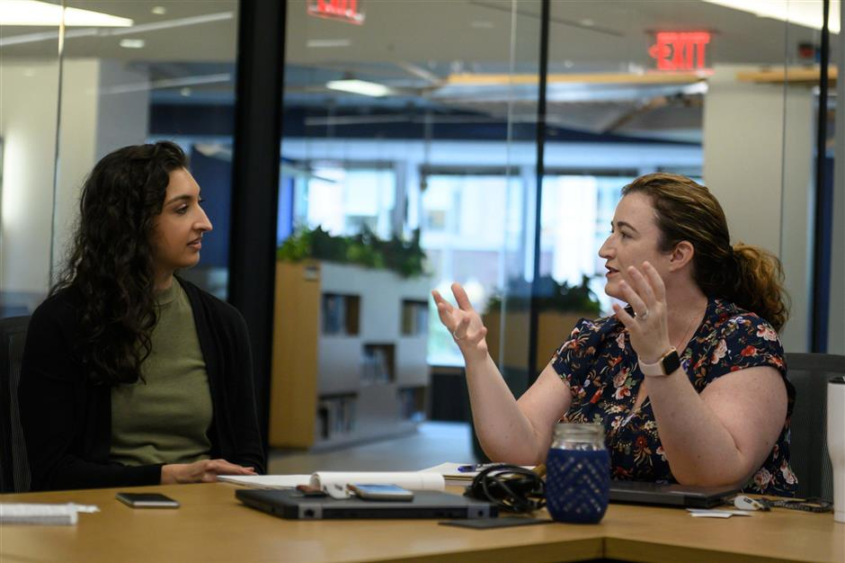 Lacey Malarky (L), an Oceana campaign manager on illegal fishing and transparency, speaks with Beth Lowell, Deputy Vice President US Campaigns, at the headquarters of the NGO Oceana on June 10, 2019 in Washington, DC. - From her desk in a building in downtown Washington, Lacey Malarky monitors fishing vessels that take advantage of the vastness of Earth's oceans to cheat in the belief that no one is watching. Malarky uses a website called Global Fishing Watch, which was launched by her employer, the NGO Oceana, with Google and a nonprofit called SkyTruth less than three years ago to trace where 70,000 fishing vessels have sailed since 2012. (Photo by Eric BARADAT / AFP)