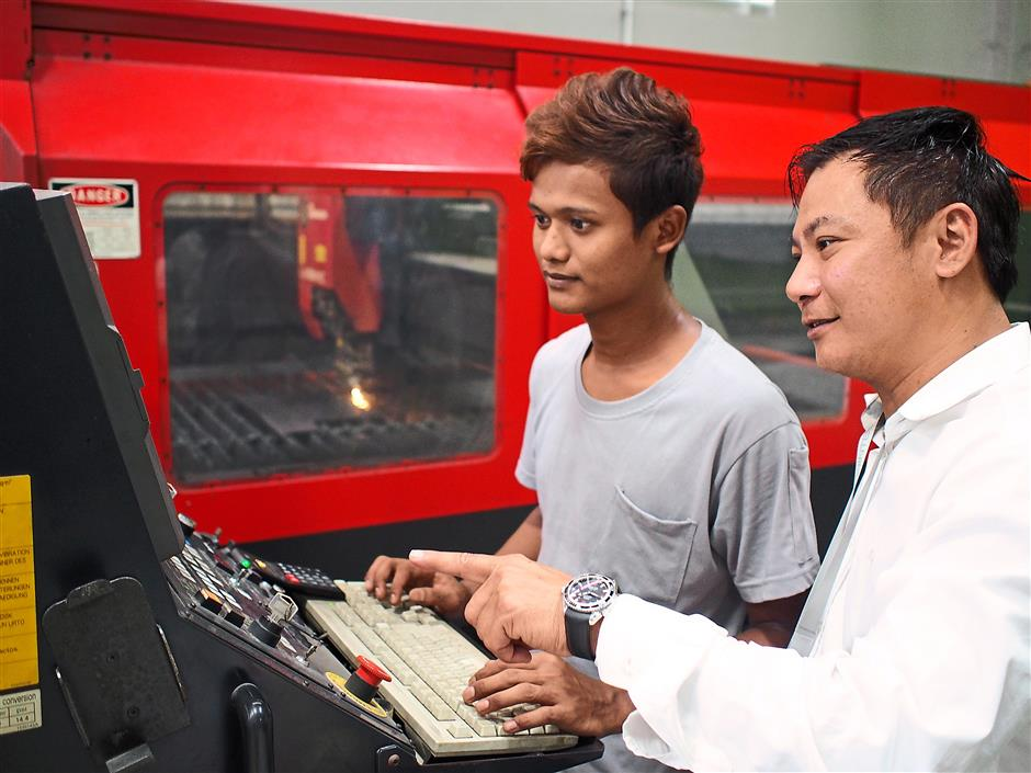 Wong discussing machine operations with one of his workers.