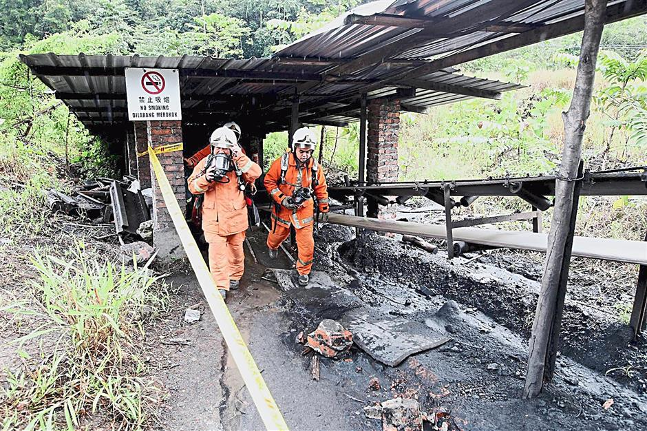 Soot and ashes: Fire and Rescue Department forensic personnel inspecting the coal mine area after the explosion. — ZULAZHAR SHEBLEE / The Star