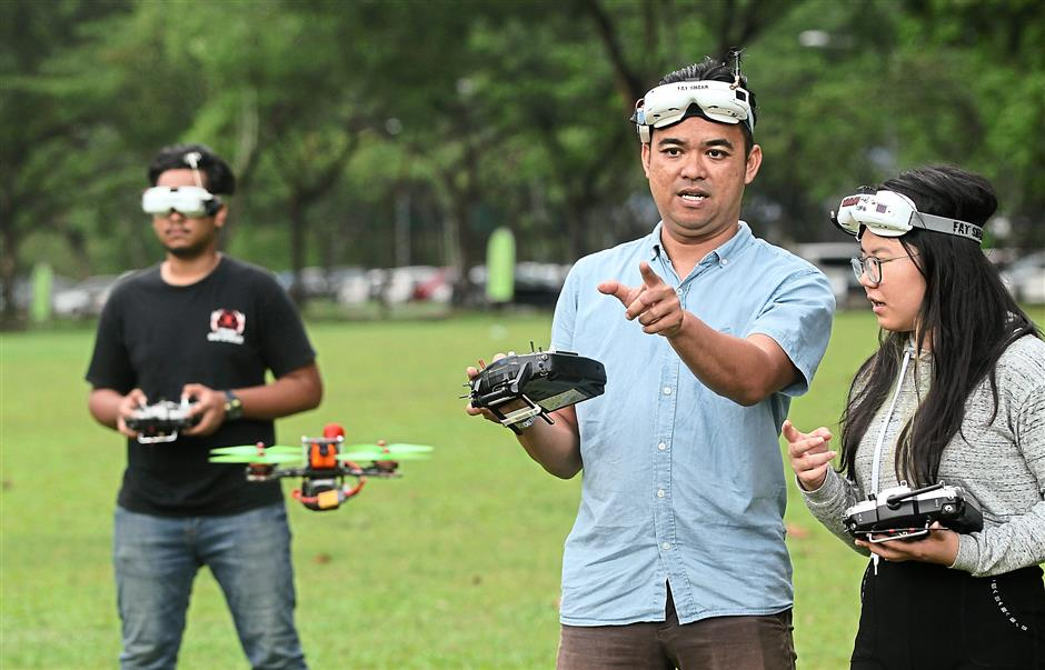 Saw (right) and Amir (left) rely on their drone racing coach Shah Johan to soup up their drones and make them competition-ready. — AZMAN GHANI/The Star