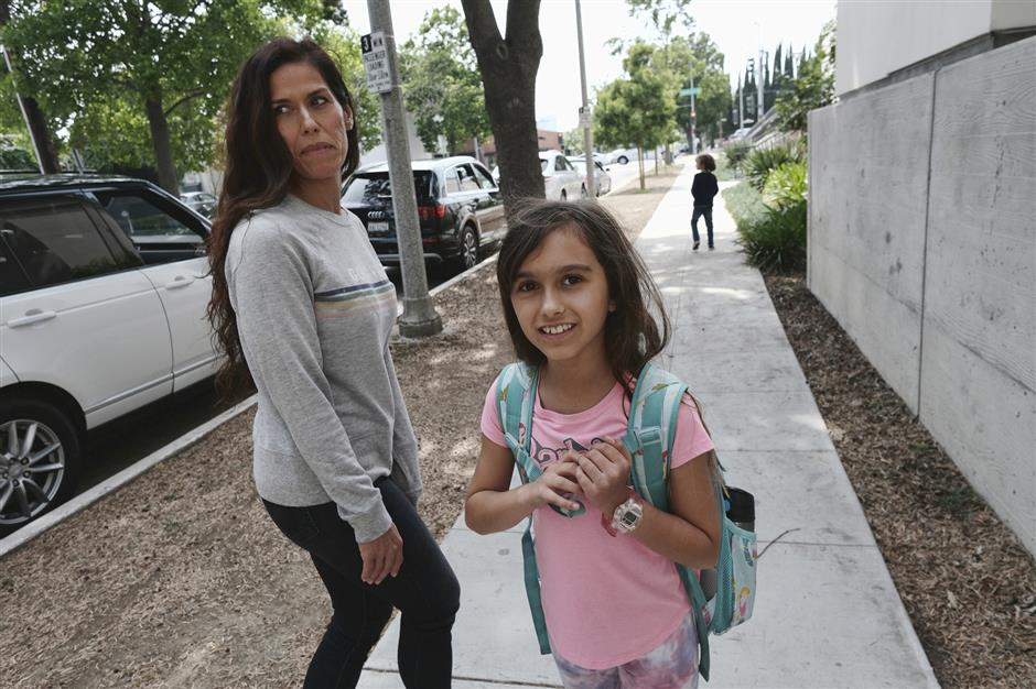 "In this Monday May 13, 2019 photo Christina Richner, walks down the street with her children Julian, far right, and Olivia at Horace Mann School in Beverly Hills, Calif. Richner, said of her children that they have gone through so many emergency drills that ""their reflexes will kick in"" during a shooting. The students are trained to gather in a corner with the classroom's lights out and blinds drawn in a lockdown situation, according to social studies teacher Laura Stark. (AP Photo/Richard Vogel)"