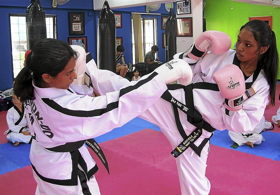 G. Marahathananggai (left) and  S. Santhia involved in a bout during a  training session.