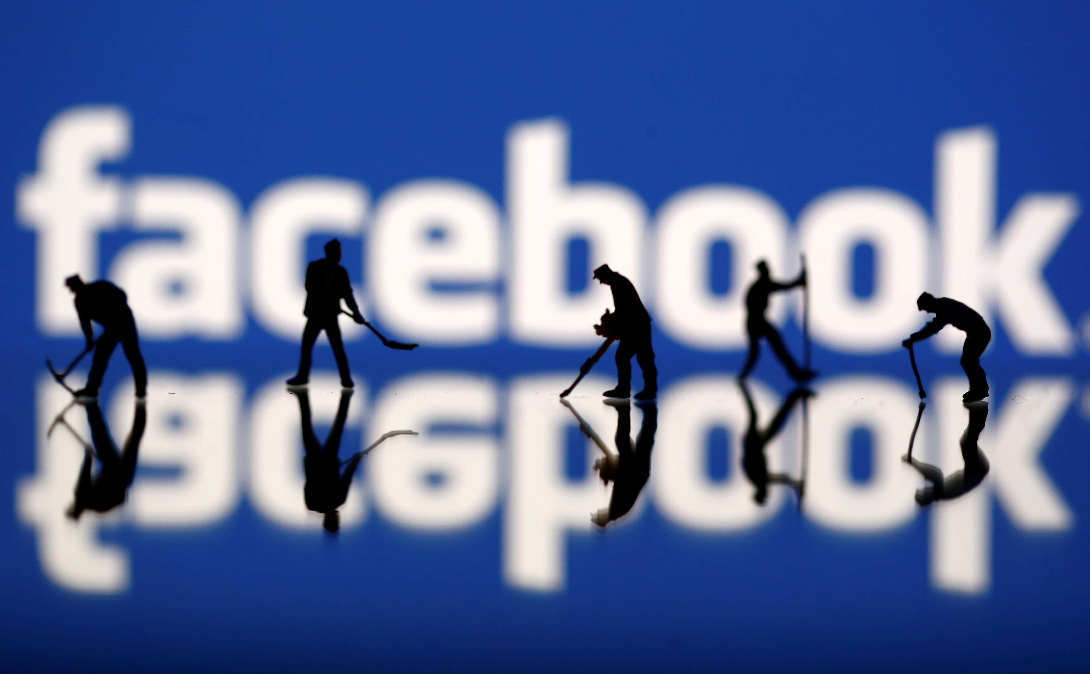 FILE PHOTO: Figurines are seen in front of the Facebook logo in this illustration taken March 20, 2018. REUTERS/Dado Ruvic