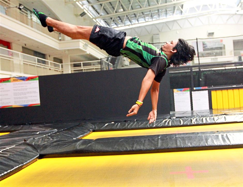 Jump referee Muhammad Tasnim Kamaruddin demonstrating how to land on the back on an Olympic specs trampoline at Jump Street Penang.