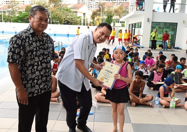 (From left) Ooi with Mak presenting a certificate of participation to Lee Yuan Xin, 10, during the closing ceremony.