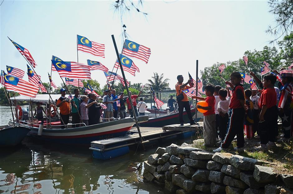 Afloat with pride: Residents of Kampung Fikri in Setiu, Terengganu, waving the Jalur Gemilang during a boat procession in conjunction with the MerdekaCommunity programme. The 1km-long procession was held as a demonstration of patriotism ahead of National Day. — Bernama