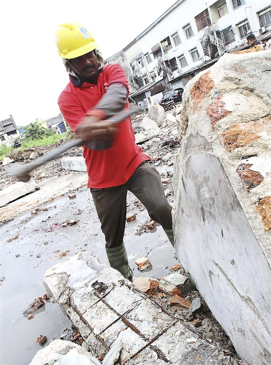Breaking it down: A worker using a sledgehammer to break a pillar of one of the shophouses being demolished on Jalan Kem.