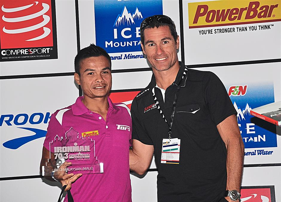Best Malaysian finisher Mohd Amran Abdul Ghani receiving his prize from Craig Alexander.