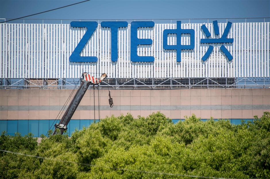 (FILES) In this file photo taken on May 3, 2018 shows the ZTE logo on an office building in Shanghai. The United States and China have a tentative deal to save embattled Chinese telecom company ZTE, days after the two nations announced a truce in their trade standoff, The Wall Street Journal reported May 22, 2018. Details remain to be hammered out, but according to the general outlines of the agreement, Washington would lift a crippling ban on selling US components to the company, which in turn would make major changes in its management, executive board and possibly pay additional fines, according to the report.  / AFP PHOTO / Johannes EISELE
