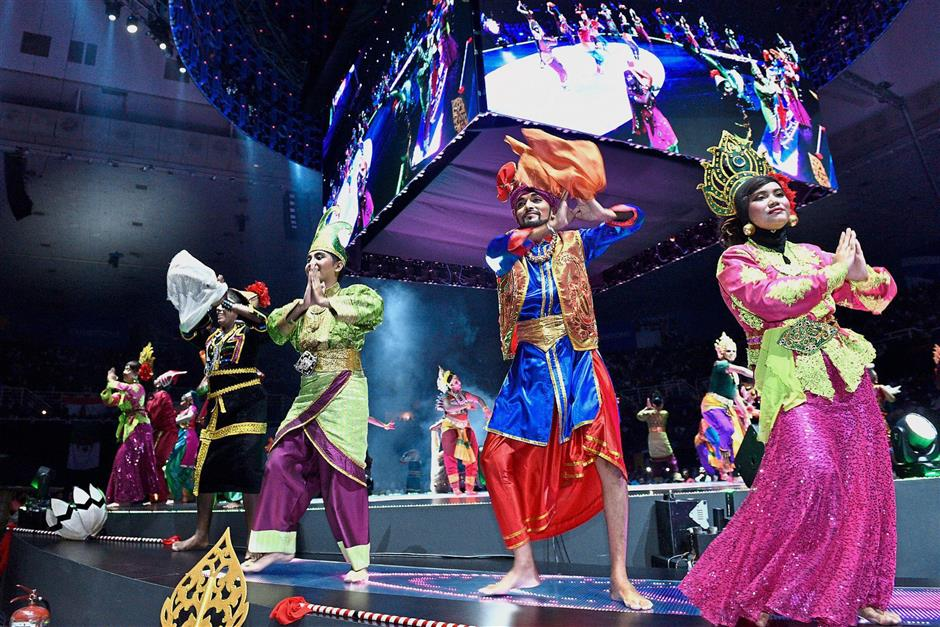 Lively stage performances entertaining the guests at QNET's V-Malaysia 2018 convention. (Right) Dr Vijay (in red) and Bismark (wearing coat) thanking the guests for their support.