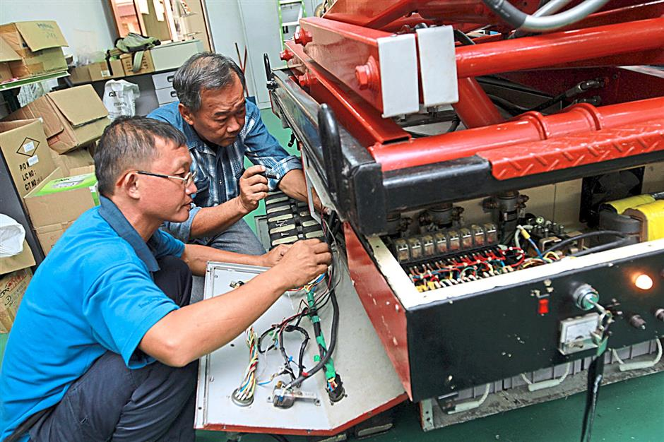 Engineers inspecting the robot's wiring  before a test run.