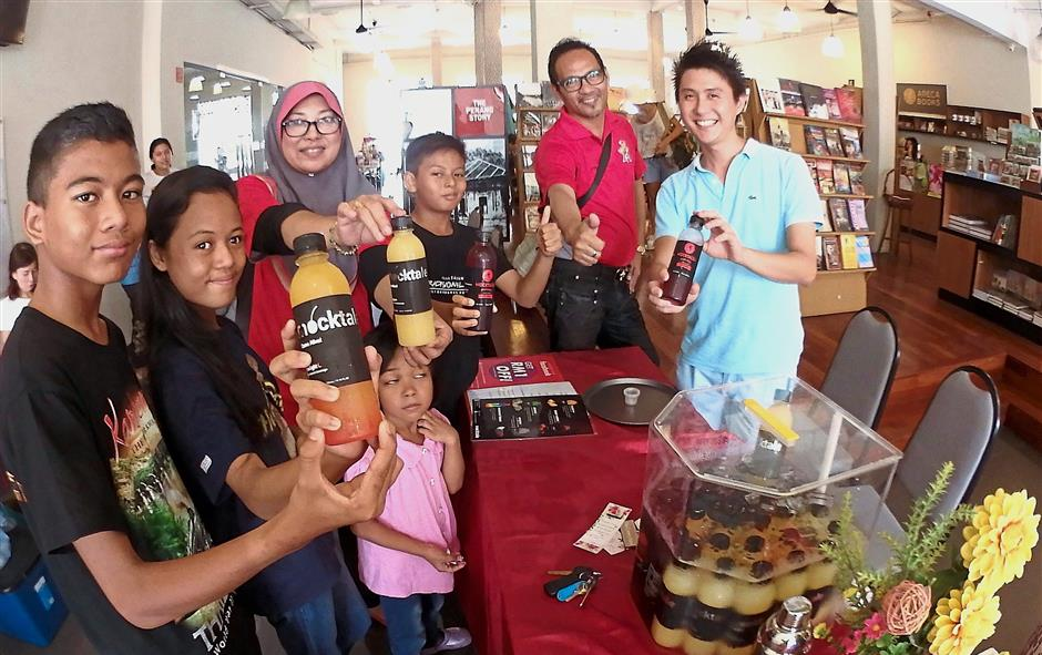 Mok (right) and visitors to his booth showing the Mocktale series of bottled fruit juices.