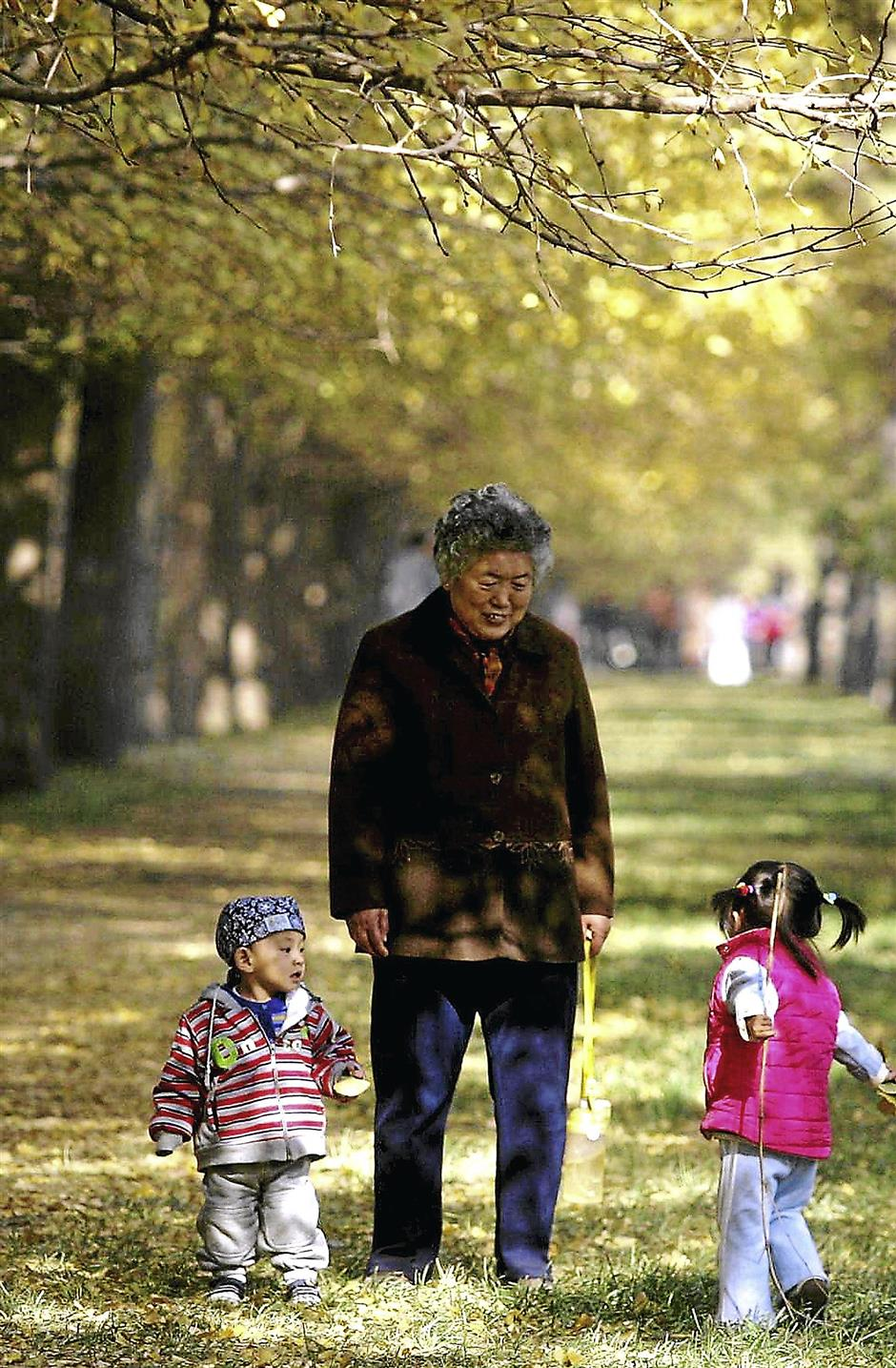 An elderly Chinese woman watches over her grandchildren as they walk along a park on a cold autumn morning in Beijing, 12 November 2005.  With 1,000 days to go before the 2008 Olympics, China is promising a Games that will make money while avoiding the twin scourges of corruption and pollution.   AFP PHOTO