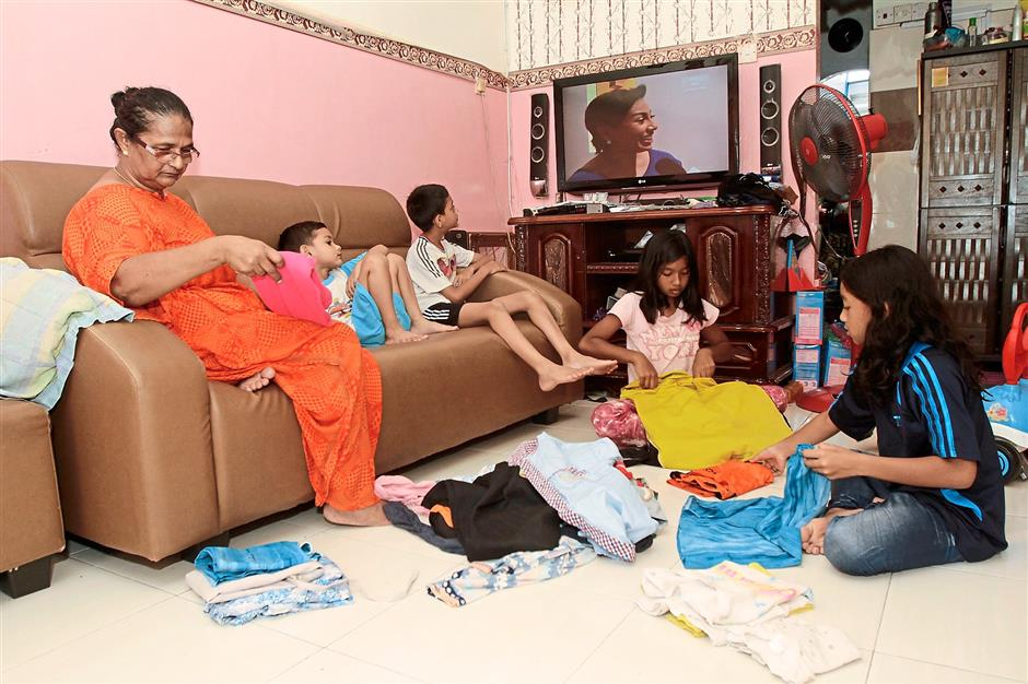 Cramped quarters: Faridah and her grandchildren watching television and folding clothes at their rented unit. There are 10 family members living in the 500sq ft flat.