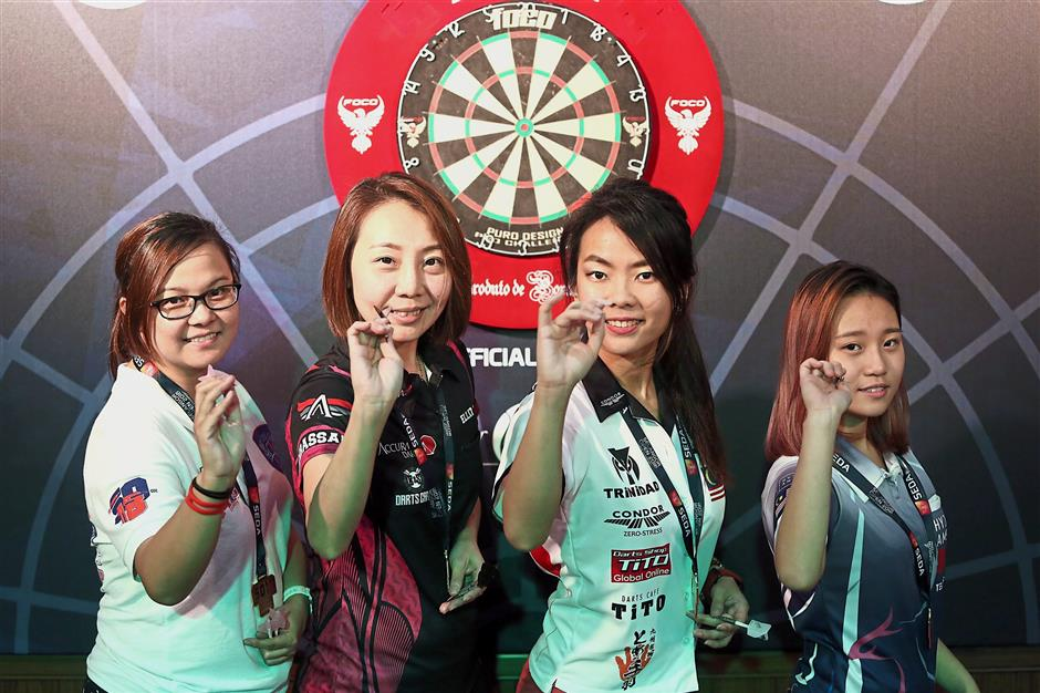 Members of Malaysia's Apache Angels (from left) Careena Hilda Carvalho, Cheok Hui Yee, Ernestine Tey and Elliz Chong posing with their darts and medals after winning joint third in the tournament.
