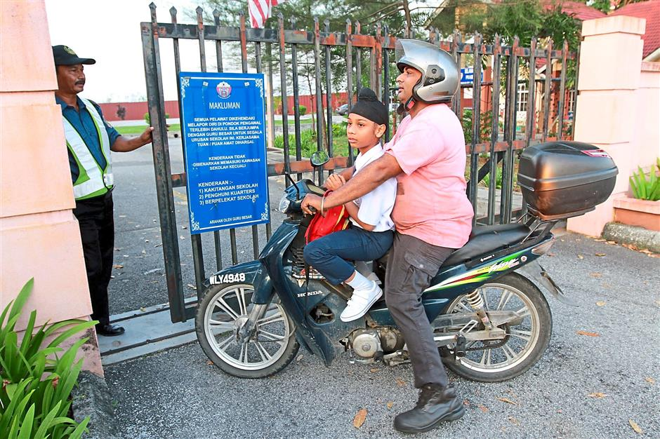Sorry, school's closed: A security guard turning a father and son away at SK Taman Sungai Besi Indah.