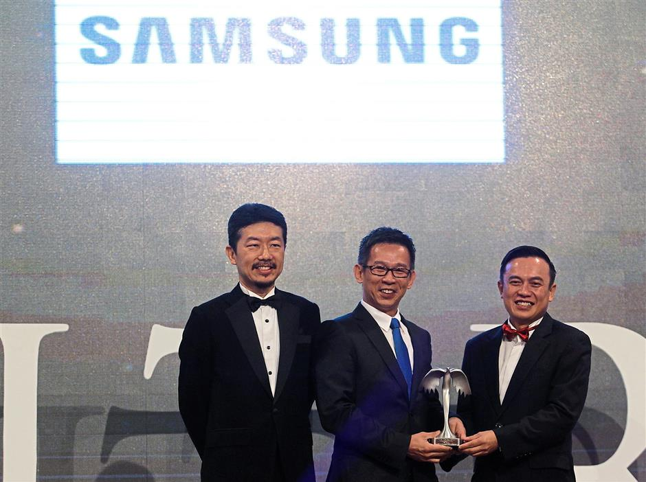 Triumphant night: Samsung Electronics head of consumer electronics business Jimmy Tan Chee Wee (centre) receiving the Gold award for the Personal, Household and Outdoor Appliances category from See Hua Marketing Sdn Bhd general manager of sales Pattrik Ting. Looking on is 4As council member Daniel Chong. Samsung Electronics had won four awards as of press time.