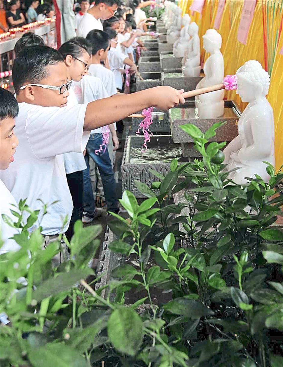 Buddhist Chempaka Lodge's Dhamma Sunday School children bathing the Buddha statues.