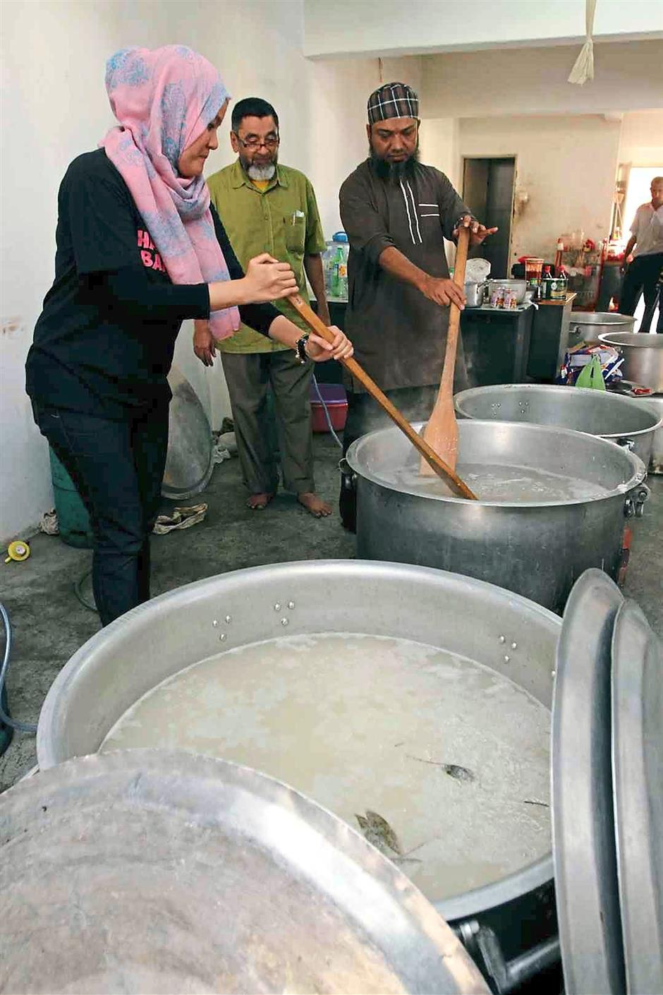 Nurainie (left) and Rafik (right) helping with the cooking at the Raya Rohingya programme while a volunteer looks on.