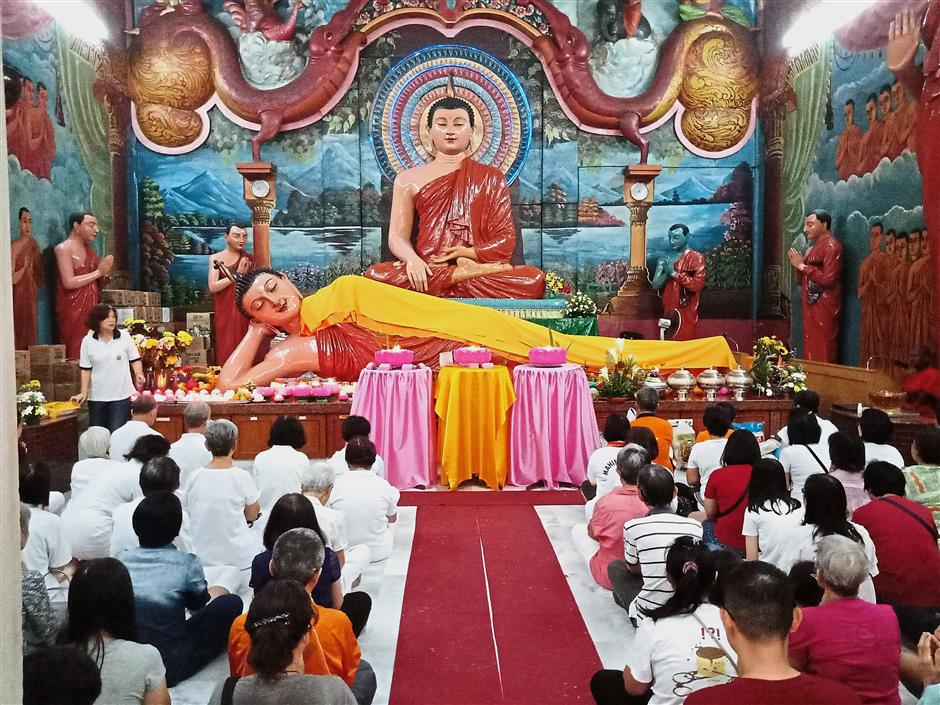 Wanting a better future: Devotees praying during Wesak Day celebration at Mahindarama Buddhist Temple in Jalan Kampar, Penang. Inset: Indaratana Maha Thera.