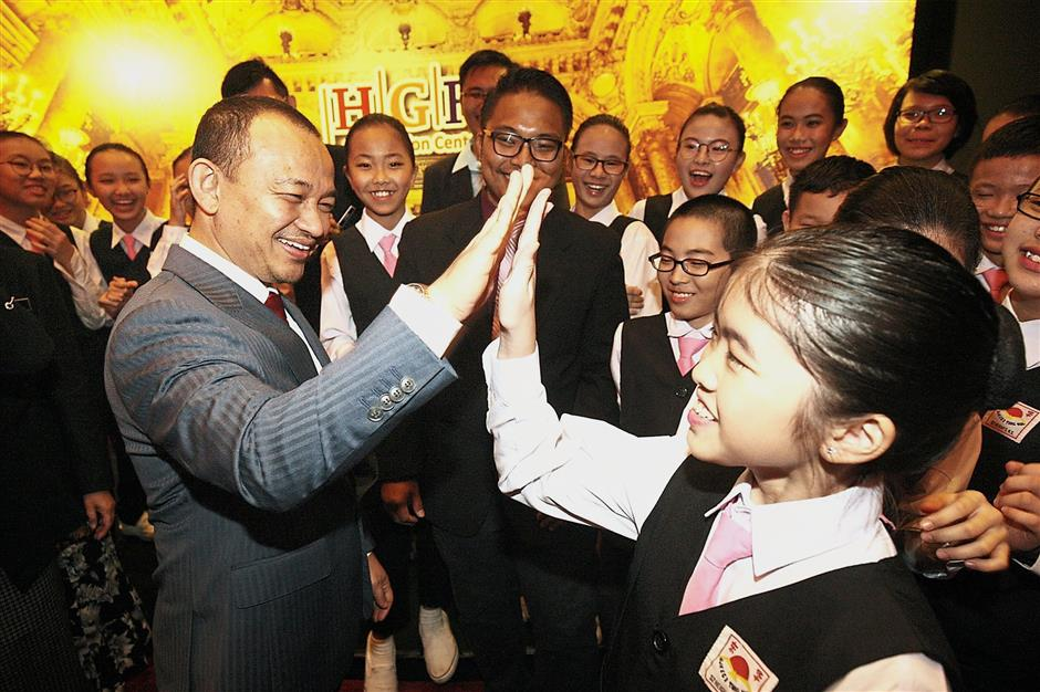 Dr Maszlee gives a student a high five after launching the Raising Bahasa Melayu Standards for Chinese vernacular schools Forum 2018.