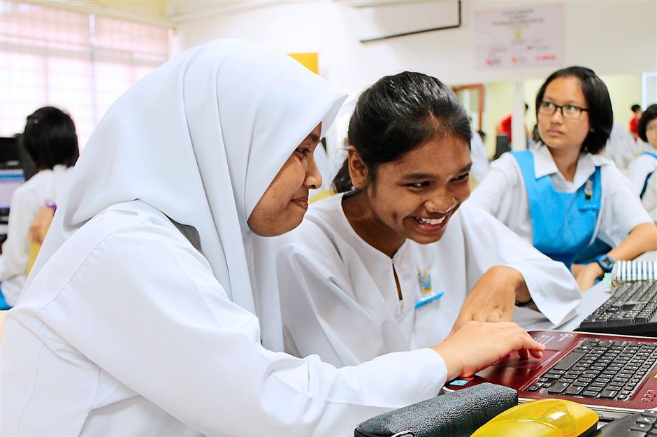 Looks easy: These girls from SMK St. Mary, seem pleased with what they see on the laptop screen during a workshop.