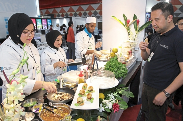 Weu2019re all set: Quest International University Perak lecturers and students busy preparing food for visitors at the booth during the Star Education Fair. (Inset) Quest student Marakrishnan Pandian, 22, showing the mix berry mousse.