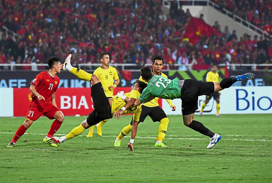 Caught in the middle: Malaysia's Mohamad Zaquan Adha Abdul Radzak is challenged by Vietnam goalkeeper Dang Van Lam in the AFF Suzuki Cup second leg final at the MyDinh Stadium yesterday. Vietnam won 1-0 to emerge champions 3-2 on aggregate. Inset: Nguyen Anh Duc celebrating after scoring in the fifth minute. — Bernama