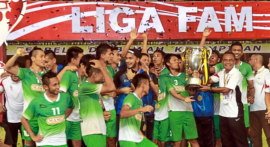 Malacca's players and coach Mat Zan (holding cup, right) celebrate with the FAM Cup.