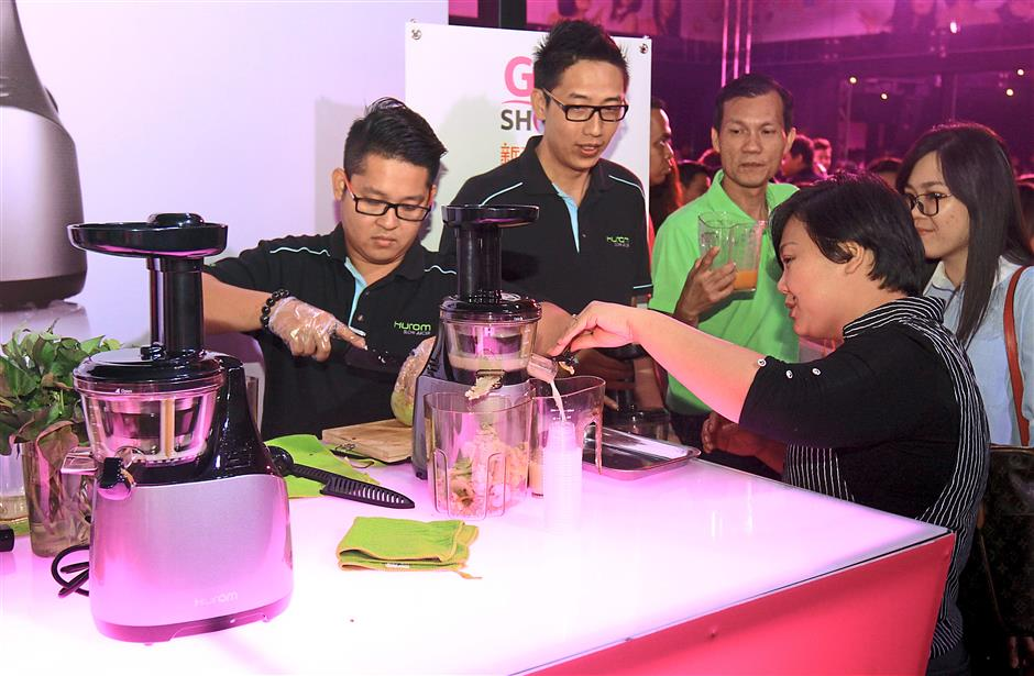 Attendees of the Astro Go Shop Channel 318 launch try their hands on the products for sale in the shopping network.