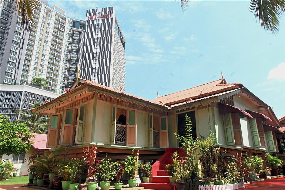 Villa Sentosa, the oldest traditional house in Kampung Morten, looks dwarfed juxtaposed against the high-rise building in the background.