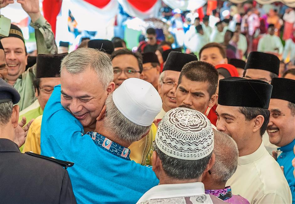 Well-loved: Sultan Nazrin Shah being hugged during a Hari Raya Aidilfitri event. — filepic