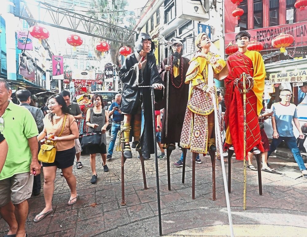 Characters from Journey to the West walking on stilts.