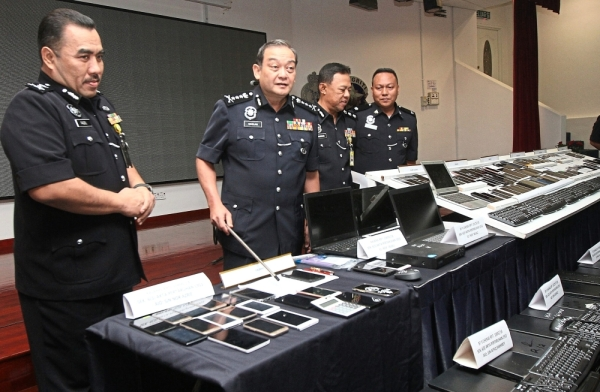 Comm Mazlan (second left) at a July 2018 press conference announcing the break up of an illegal World Cup betting ring. With him is SAC Fadzil Ahmat (left).