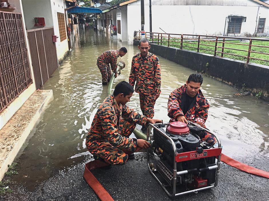 Fire and Rescue Services personnel pumping water out from the flooded houses in Hong Seng Estate, Mount Erskine.