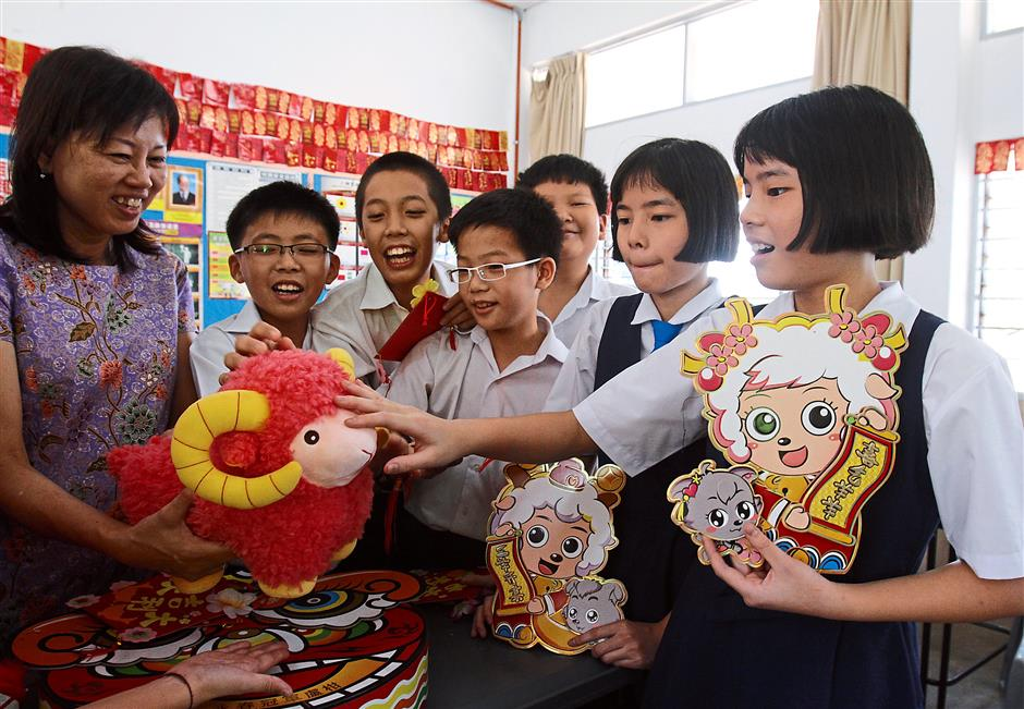 Valuable lesson: Lam (left) explaining the symbolic meaning of the ram to twins An Xuan and An Xin (right), and her pupils at the school in Burmah Road.