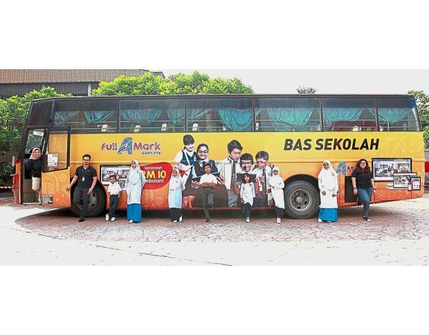 Students and NSTPu2019s team members beside a bus advertising FullAMark. With them is Farah Ezrin (left, inside the bus) at NSTPu2019s Balai Berita in Bangsar.