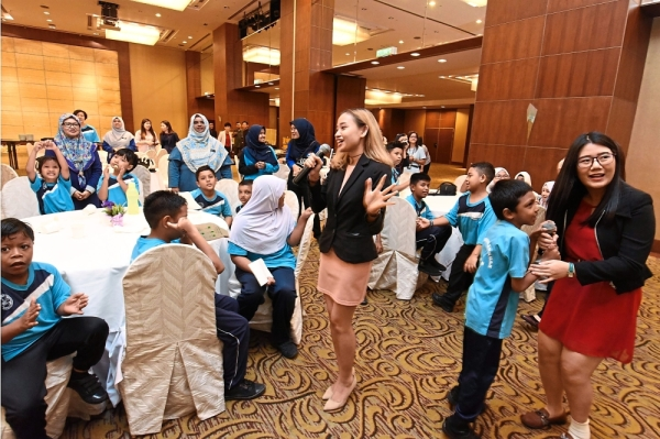 Hotel staff members getting some of the special children to join in a  sing-along session.