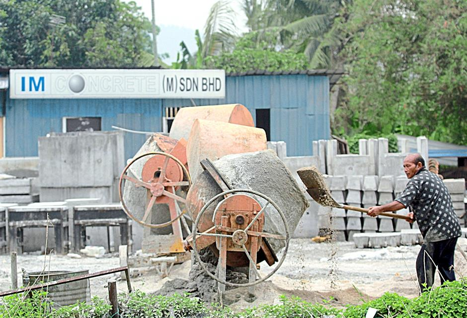 A worker mixing the materials to manufacture the glazed concrete drain.