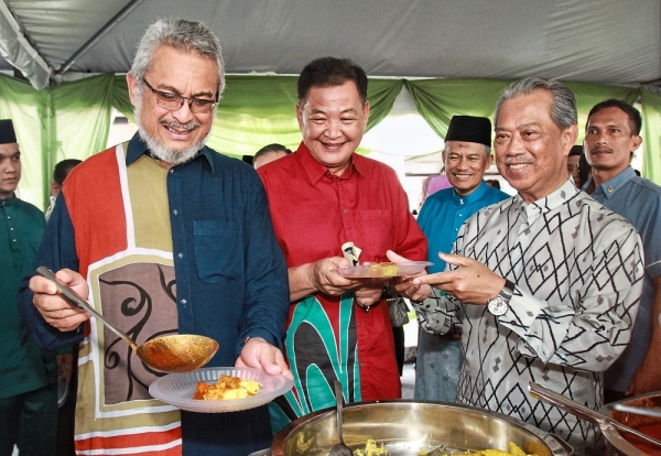 Happy meals: (From left) Khalid,  Abdul Hamid and Muhyiddin helping themselves  to roti jala  during  the PDRM  and Federal Territories Ministry  Hari Raya event  at the Police  Training Centre.