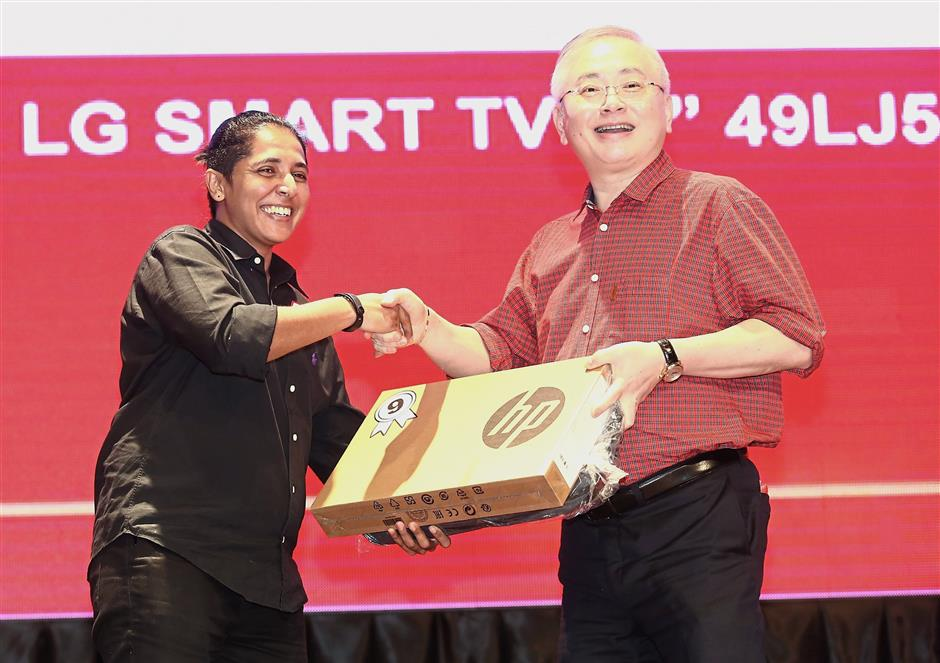 Dr Wee (right) presenting a HP laptop to one of the lucky draw winners, StarTV video executive Juliana Mohd Fauzi.