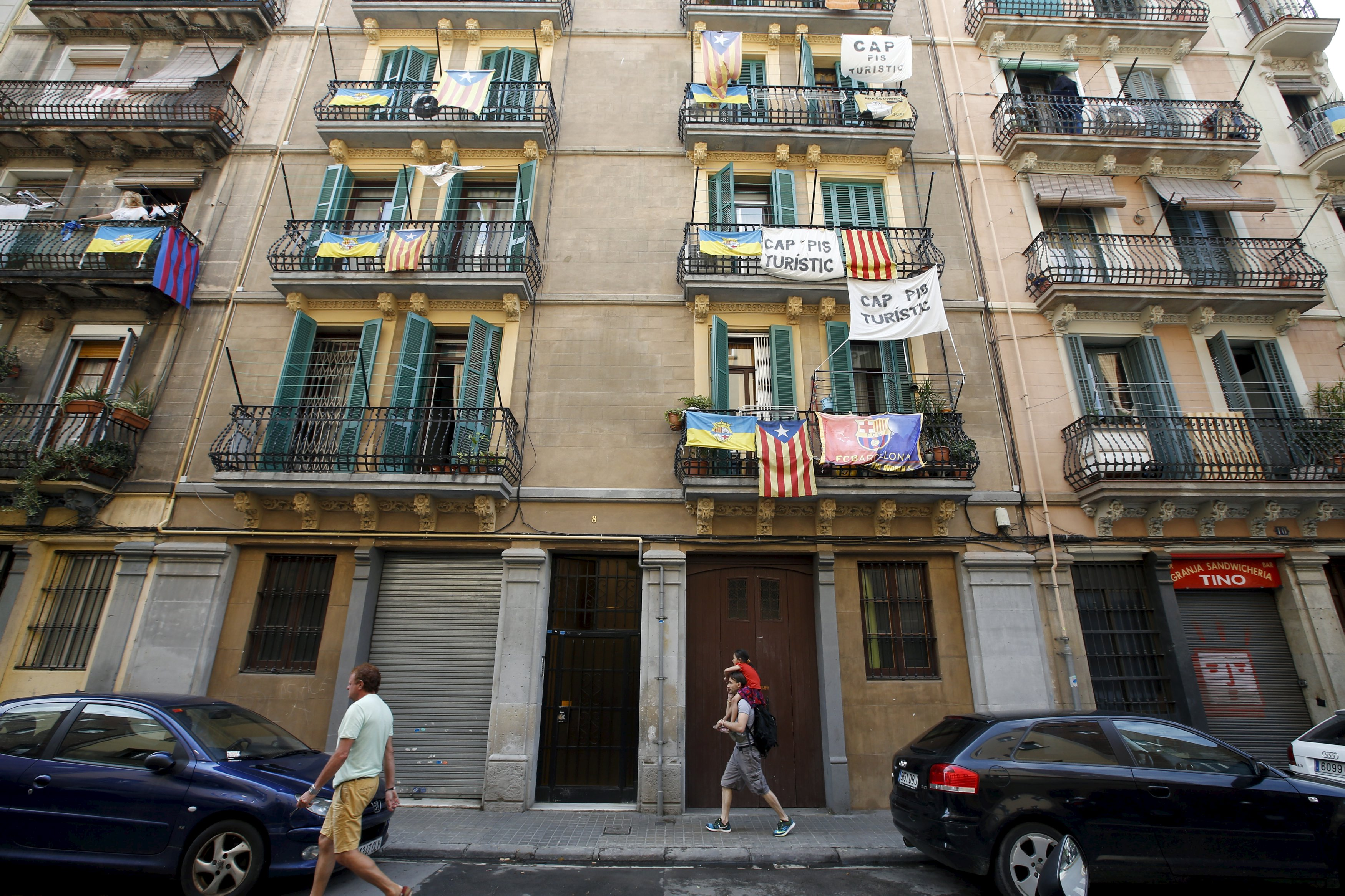 Banners against touristic apartments hang from balconies as people walk past them at Barceloneta neighborhood in Barcelona, Spain, August 18, 2015.  REUTERS/Albert Gea