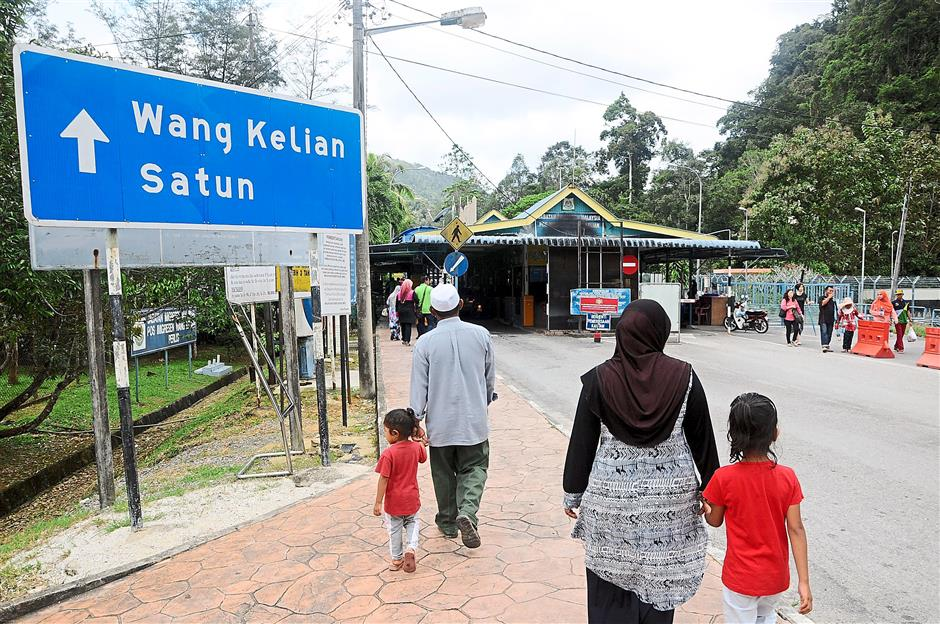 Visitors walking towards the Malaysia Immigration check-point in Wang Kelian, Perlis yesterday.