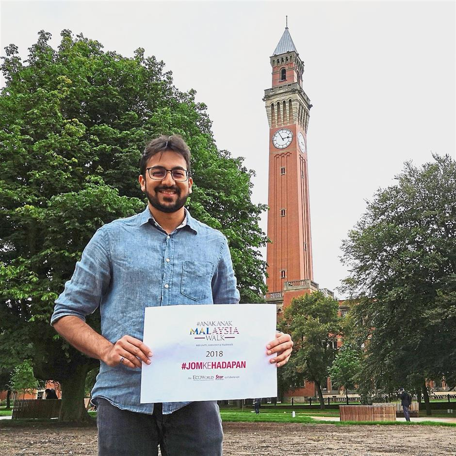 Hello from the UK: Akil in front of the Joseph Chamberlain Memorial Clock Tower at the University of Birmingham.